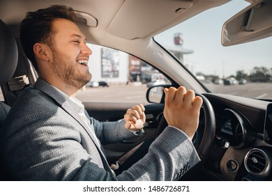 Happy driver in a suit dancing in his luxary car listening to music and enjouying life. Concept of success.