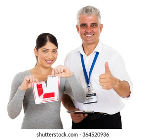 happy driving instructor giving thumb up and learner driver tearing L sign