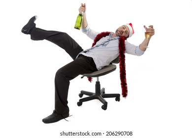 Happy drunk businessman wearing santa hat with tinsel around his neck in blue business shirt and tie holding bottle and glass of champagne drinking sitting in office  office chair at christmas party