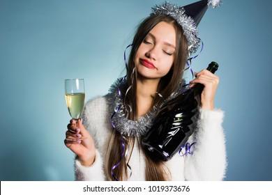 happy drunk woman in a festive cap holding a bottle in her hand