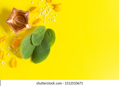 Happy Dussehra. Clay Diya lamps lit during Dussehra with yellow flowers, green leaf and rice on yellow background. Dussehra Indian Festival concept.