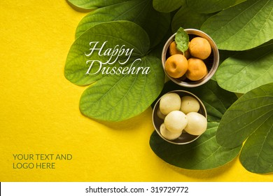 Happy Dussehra greeting card using apta  / Bauhinia racemosa / Bidi leaf and indian sweet pedha or pera