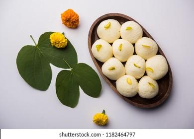Happy Dussehra / Vijayadashami / Ayudh Puja greeting card using apta/Bauhinia racemosa/Bidi leaf and indian sweet Rasgulla for Navaratri