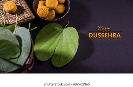 Happy Dussehra / Vijayadashami / Ayudh Puja greeting card using apta/Bauhinia racemosa/Bidi leaf and indian sweet pedha or pera