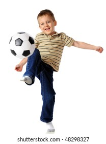 A happy, early elementary boy kneeing a soccer ball.  Isolated on white.  (Motion blur on the ball.