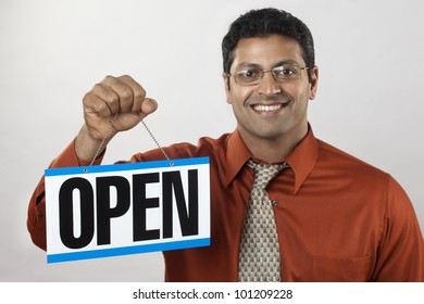 Happy East Indian business owner holding an Open Sign