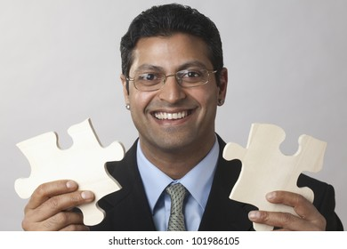 Happy East Indian Businessman holding puzzle pieces