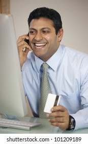 Happy East Indian businessman on the phone with credit card at his computer