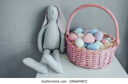 Happy Easter! A basket full of colorful painted Easter eggs and toy bunny are standing on the table.