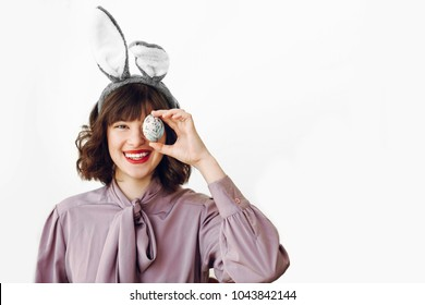 happy Easter. beautiful stylish girl in bunny ears holding colored easter egg on white background isolated. funny easter hunt concept. happy woman smiling with egg at face. fun moments