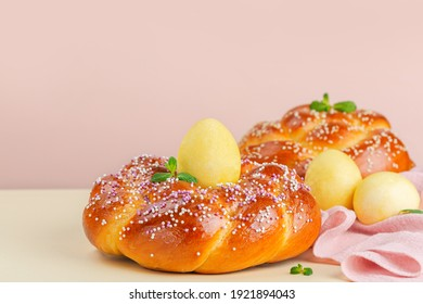 Happy Easter. Easter bread and Easter eggs on light peach and yellow background decorated with mint. Copy space.