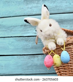 Happy Easter Bunny in a basket and eggs on a blue wooden background.