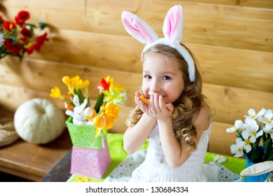 Happy easter bunny girl with colorful eggs sitting in country house and celebrating holiday
