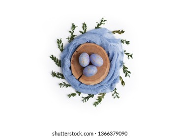 Happy easter card. Creative nest made of pastel colored textile and wooden slice with blue speckled eggs and green branches. Flat lay. Copy space for text.