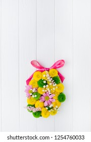 Happy Easter card. Easter egg made from flowers on white wooden background with blank space for text. Top view, flat lay.