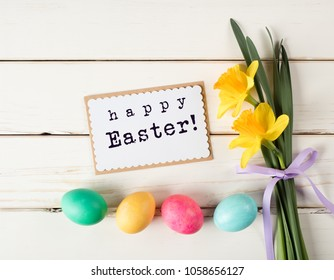 Happy Easter Card with Eggs in a Row on Bottom with Daffodil Flowers on the side of White Shiplap Board Background with room or space for copy, text, words or design.  A Horizontal with flat layout