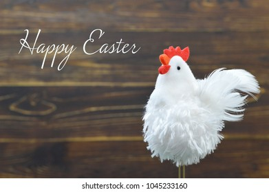 Happy Easter card with rooster toy on wooden background
