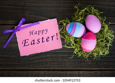 Happy Easter card with three Easter Eggs in Dyed Pink, Blue, lavender and Purple in green nest on rustic dark wood background.  Horizontal flat lay photo from looking down above view