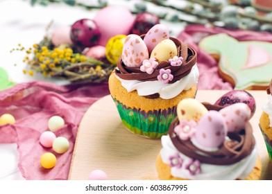 Happy Easter card: Easter vanilla cupcakes decorated with candy eggs in nest on Easter dinner table; selective focus