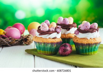 Happy Easter card: Easter vanilla cupcakes decorated with candy eggs in nest on white wooden background; selective focus, copy space