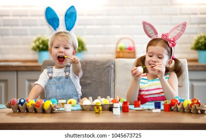 Happy easter! children girl and boy paints eggs