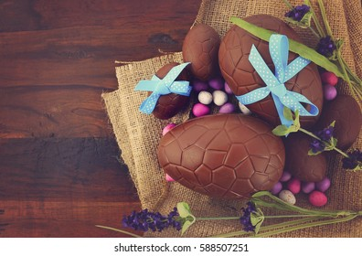 Happy Easter chocolate Easter eggs on dark wood country style table background, with applied retro style filters.