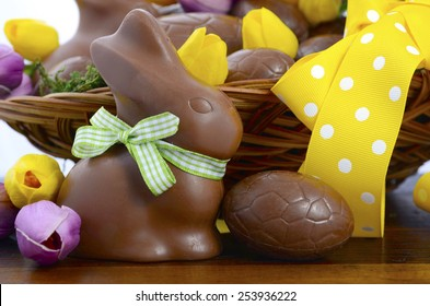 Happy Easter chocolate hamper of eggs and bunny rabbits in large basket with yellow and pink purple silk tulip flowers on dark wood table, closeup.