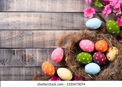 Happy easter! Colourful of Easter eggs in nest with pink flower and Feather on wooden background.