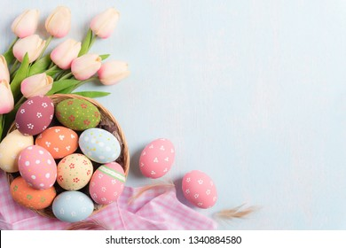 Happy easter! Colourful of Easter eggs in nest with Pink tulips and Feather on blue sky wooden background.