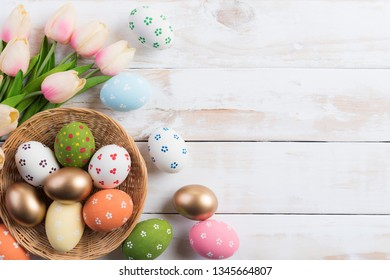 Happy easter! Colourful of Easter eggs in nest with pink tulip flower and Feather on wooden background.