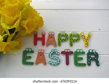 Happy Easter in colourful wooden letters beside a  bunch of Spring daffodils against a white wooden  background.