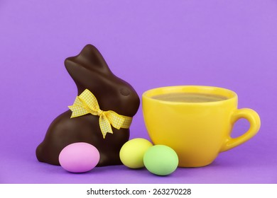 Happy Easter concept - bright yellow cup of cappuccino coffee with a chocolate Easter bunny decorated with a bow and three colourful confectionery Easter eggs on purple background