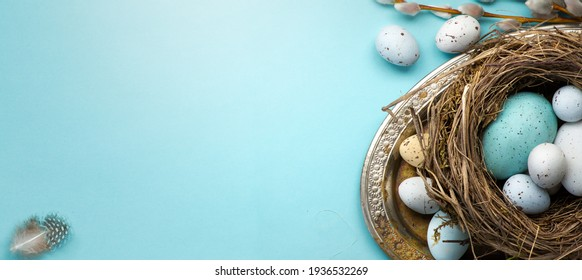 Frohe Ostern Konzept. Rahmen aus Ostereiern und Frühlingsblumen auf blauem Hintergrund. Flachlage, Draufsicht, Kopienraum.