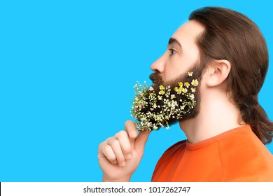 Happy Easter concept. Nice kind muscle man male with beard and spring's flowers in orange t-shirt isolated on blue background. Spring time concept
