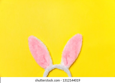 Happy Easter concept. Preparation for holiday. Decorative bunny ears furry fluffy costume toy isolated on trendy yellow background. Simple minimalism flat lay top view copy space