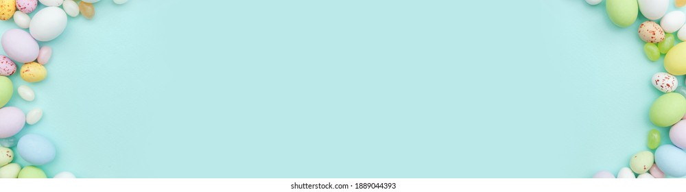 Happy Easter concept. Preparation for holiday. Easter candy chocolate eggs and jellybean sweets isolated on trendy pastel blue background. Simple minimalism flat lay top view copy space banner - Shutterstock ID 1889044393