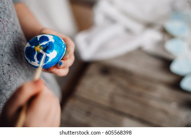 Happy easter! Cute little child girl painting with blue and yellow colors Easter eggs. family preparing for Easter. Hands of a girl with a easter egg. close-up