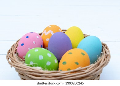 Happy Easter Day. Easter eggs concept. Closeup Colorful Easter eggs in nest and basket on white wooden background.