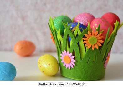Happy Easter Day. Easter eggs concept. Closeup Colorful Easter eggs in nest and basket green crass on white wooden background.