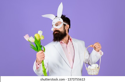 Happy Easter! Easter day. Spring holidays. Egg hunt. Easter bunny costume. Easter concept. Bearded man in bunny mask holds eggs. Man in bunny mask. Rabbit man. Flowers bouquet. Man with tulips. Spring