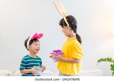 Happy easter day.asian sibling boy girl hunt eggs at home.Online easter holidays.Kids child with colorful eggs.sister brother playing easter egg hunt.Lockdown, covid19, spring.Stay home.Medical health