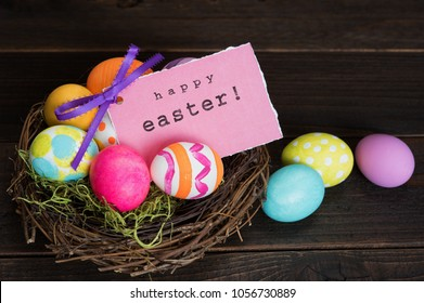 Happy Easter Eggs and Card in a nest on dark rustic wood background with room or space for copy, text, or your words.  It's a Bright and colorful horizontal photo taken from high angle view