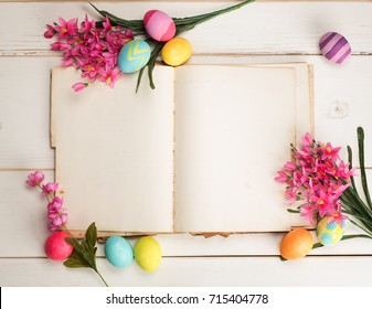 Happy Easter Eggs Card with an Open Book with Blank Paper Pages with room or space for copy, text, wording, all on shabby chic white shiplap board background or table from above, looking down view.