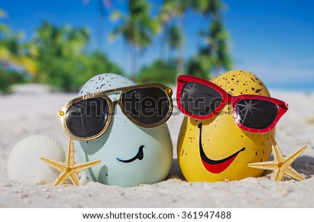 Happy easter eggs with sunglasses on ocean beach