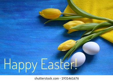 Happy Easter eggs and tulips flowers flat lay on a blue background spring holiday