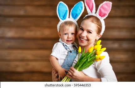 Happy easter! family mother and baby in rabbit ears with yellow tulips flowers on a wooden background