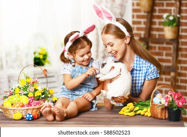 Happy easter! family mother and child daughter playing with a rabbit and and decorate home for the holiday