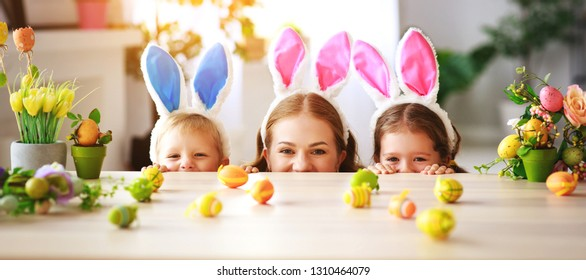 Happy easter! family mother and children with ears hare getting ready for holiday
