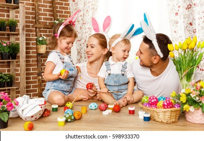 Happy easter! family mother, father and children having fun paint and decorate eggs for holiday