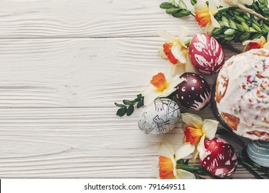 happy easter flat lay, stylish easter bread and painted eggs on rustic wooden background top view with candle yellow flowers and greenery.  greeting card. space for text